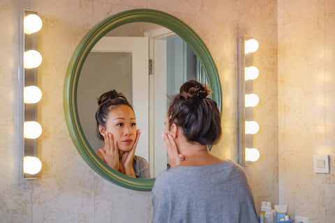 Woman inspecting skin in mirror