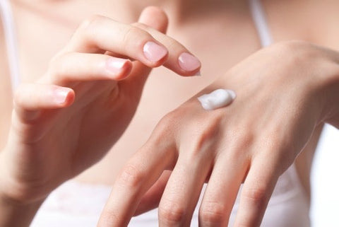 woman applying moisturizer to avoid age spots on your hands