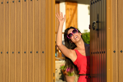 woman smiling and waving out of wooden gate