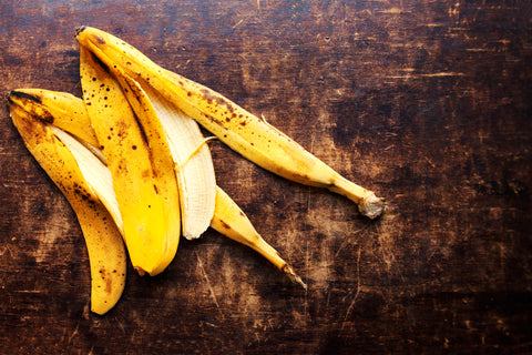 ripe banana peels on wooden background