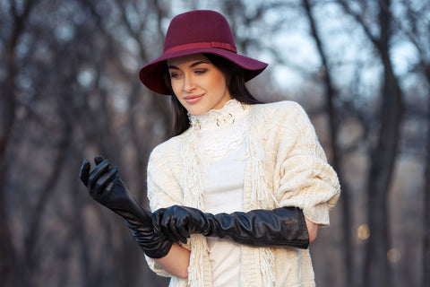 woman wearing sweater, gloves, and hat outdoors
