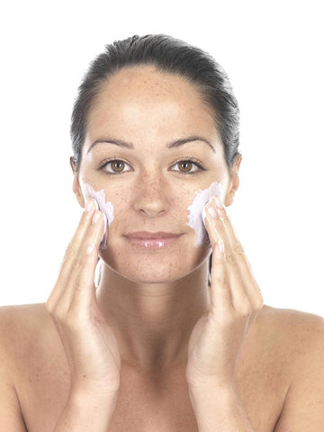 young woman exfoliating before an at-home facial