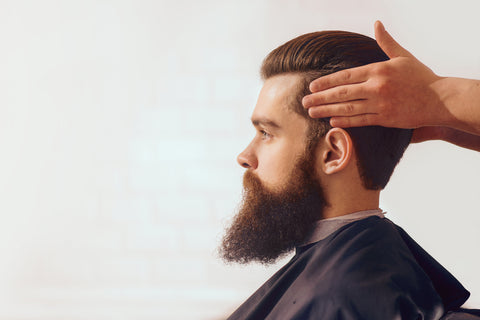 profile of man with beard in barber's chair