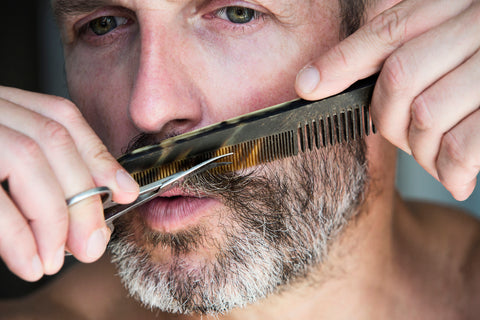 close-up of man grooming his facial hair and practicing good beard care
