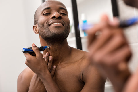 reflection of man smiling while shaving neck hair