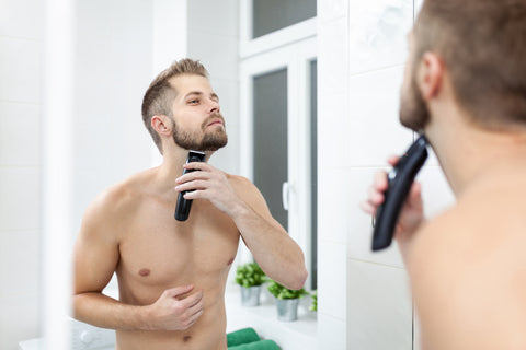 man trimming his neck hair in mirror