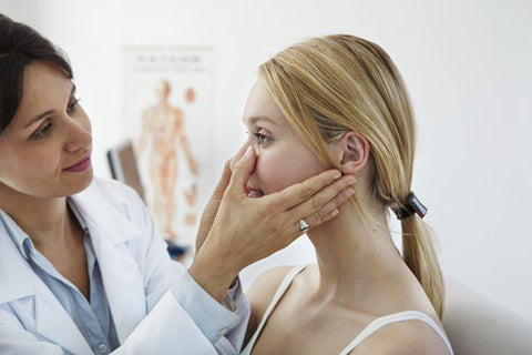 dermatologist examining woman's skin before applying a chemical peel treatment