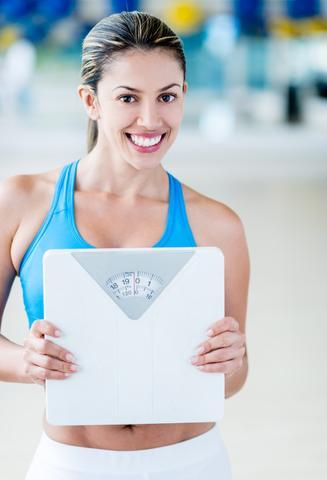 woman holding scale after exercising to prevent crepey skin