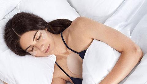 woman wearing SiO patches while sleeping to prevent and treat crepey skin