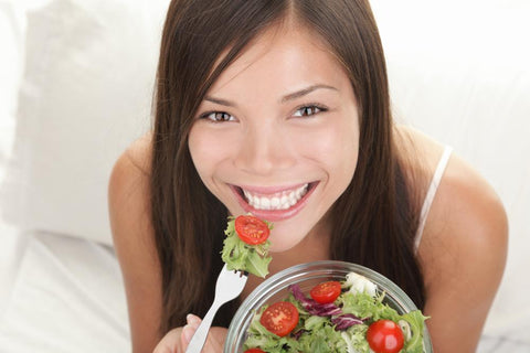 young, smiling woman eating a salad