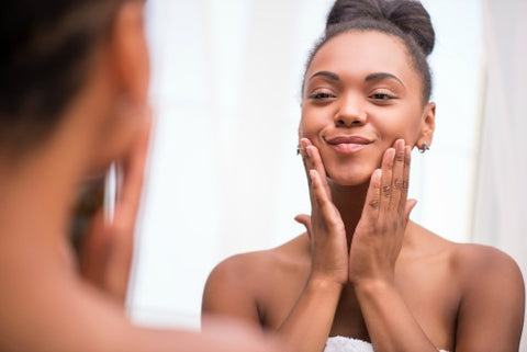 woman smiling while looking at her dewy skin in the mirror