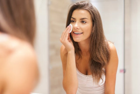 woman using cotton pad to remove makeup while looking in the mirror