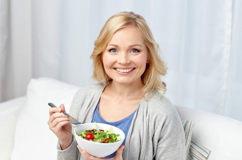 woman smiling while eating a bowl of salad on white sofa