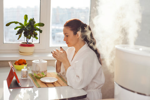 woman reading from tablet next to humidifier