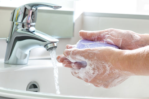 hands lathered with soap and running water in background