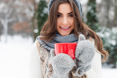 woman in warm clothing holding a mug
