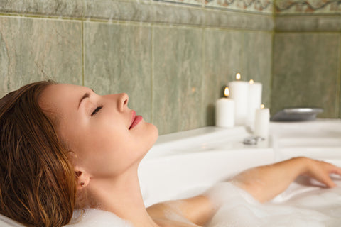 woman relaxing in bubble bath with candles in the background
