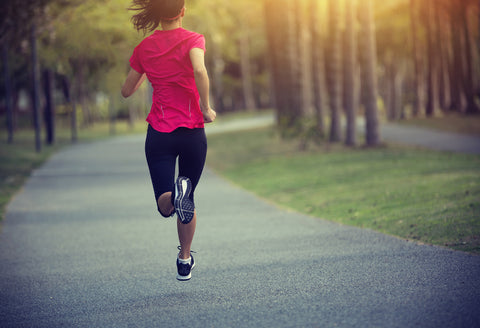 back view of woman running along path outdoors