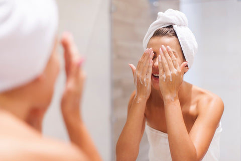woman in a towel applying cleanser to her face