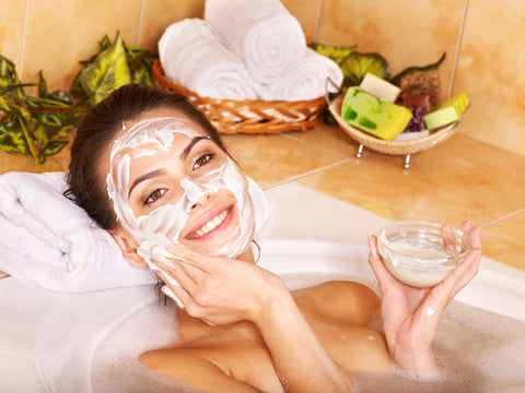 woman relaxing in a bath and applying yogurt mask to her face