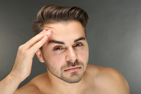 man examining forehead closely in mirror