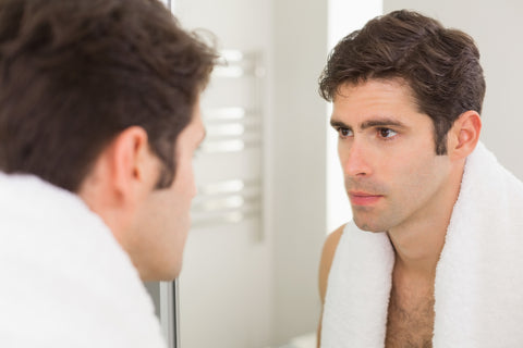 man with towel hanging around neck looking in the mirror