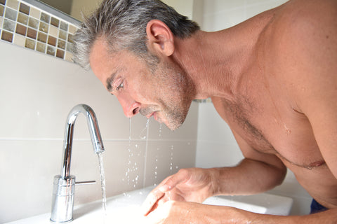 man leaning over sink with water dripping from his face