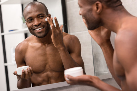 man smiling while applying cream to his cheek in the mirror