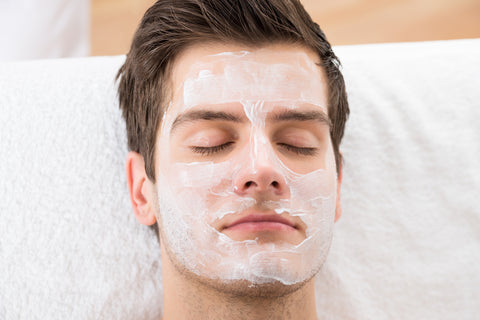 man relaxing on a white towel with a mask on his face