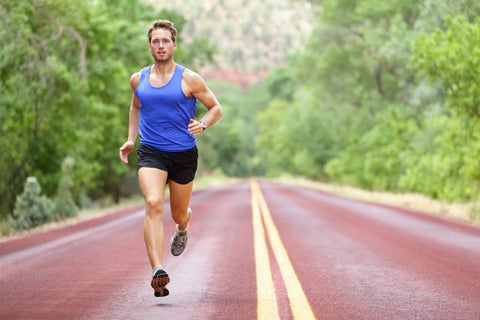man in shorts and tank jogging down a road