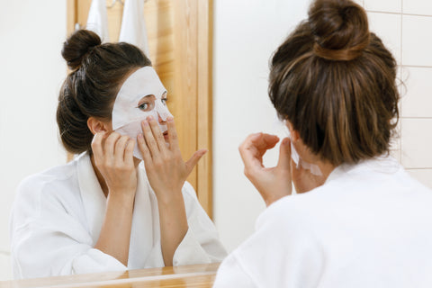 woman looking in a mirror while applying a sheet mask