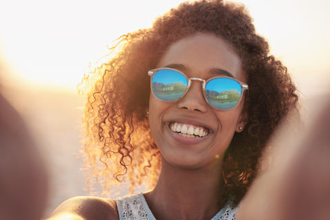 happy woman outdoors wearing sunglasses