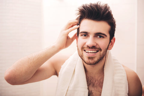 smiling man with towel around neck and hand in his hair
