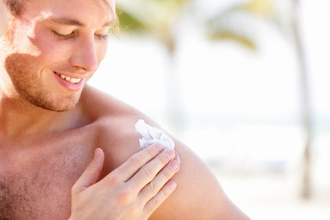 man outdoors applying sunscreen to upper arm