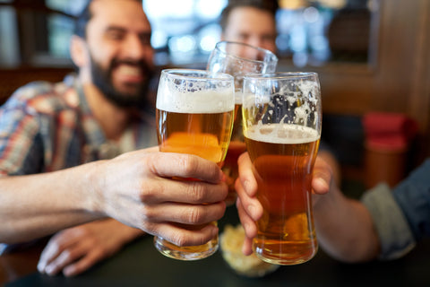 men smiling and holding up glasses of beer