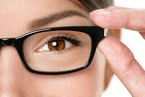 close up of woman grasping the rim of her glasses