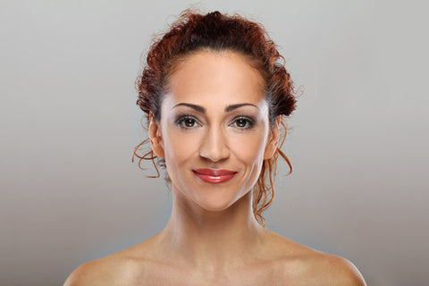 headshot of content woman with red lips and auburn hair pulled back