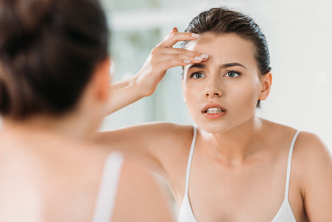 woman touching her forehead and examining her skin in a mirror