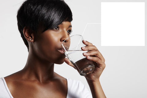 side view of a woman drinking water which is the difference between hydrating vs moisturizing