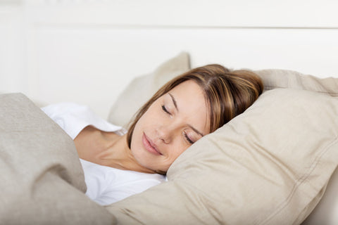 woman sleeping contently on fluffy pillows and bedding