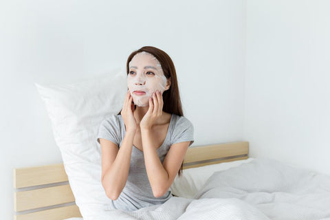 woman sitting on bed applying a Japanese skin care sheet mask