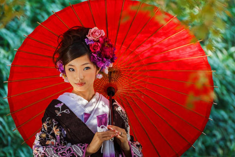 Beautiful Japanese woman holding a bright umbrella