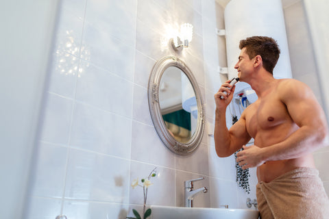 man in towel shaving in mirror