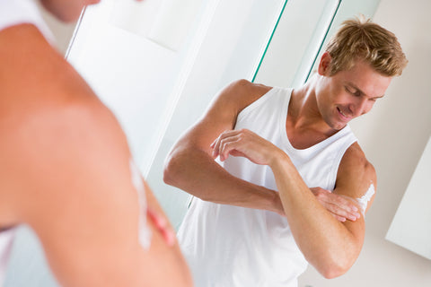 reflection of man applying scrub to upper arm