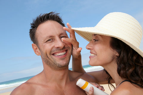 man and woman smiling as woman applies sunblock to man's nose