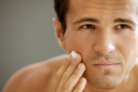 close-up of man applying exfoliation product to his face