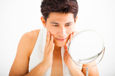 man with towel draped around neck looking in a mirror after completing men's exfoliation routine