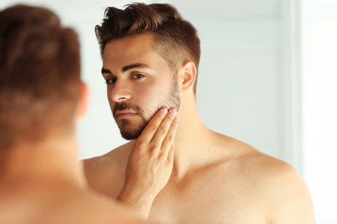 man touching and examining the side of his face in the mirror