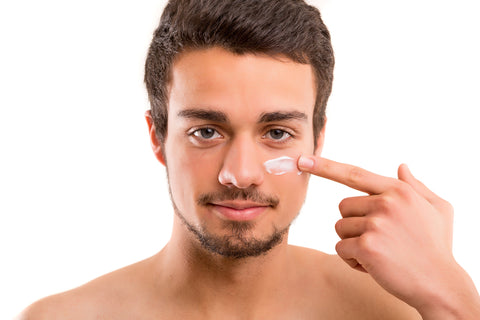 man swiping skin cream onto cheek with one finger