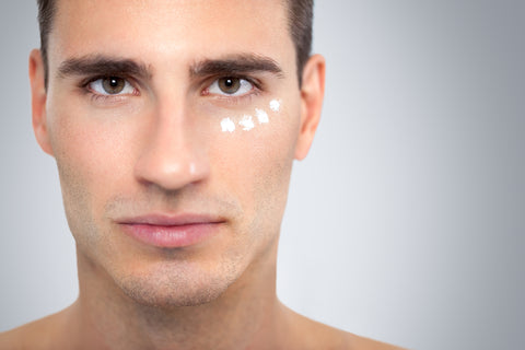 close up of man with eye cream dotted under his eye